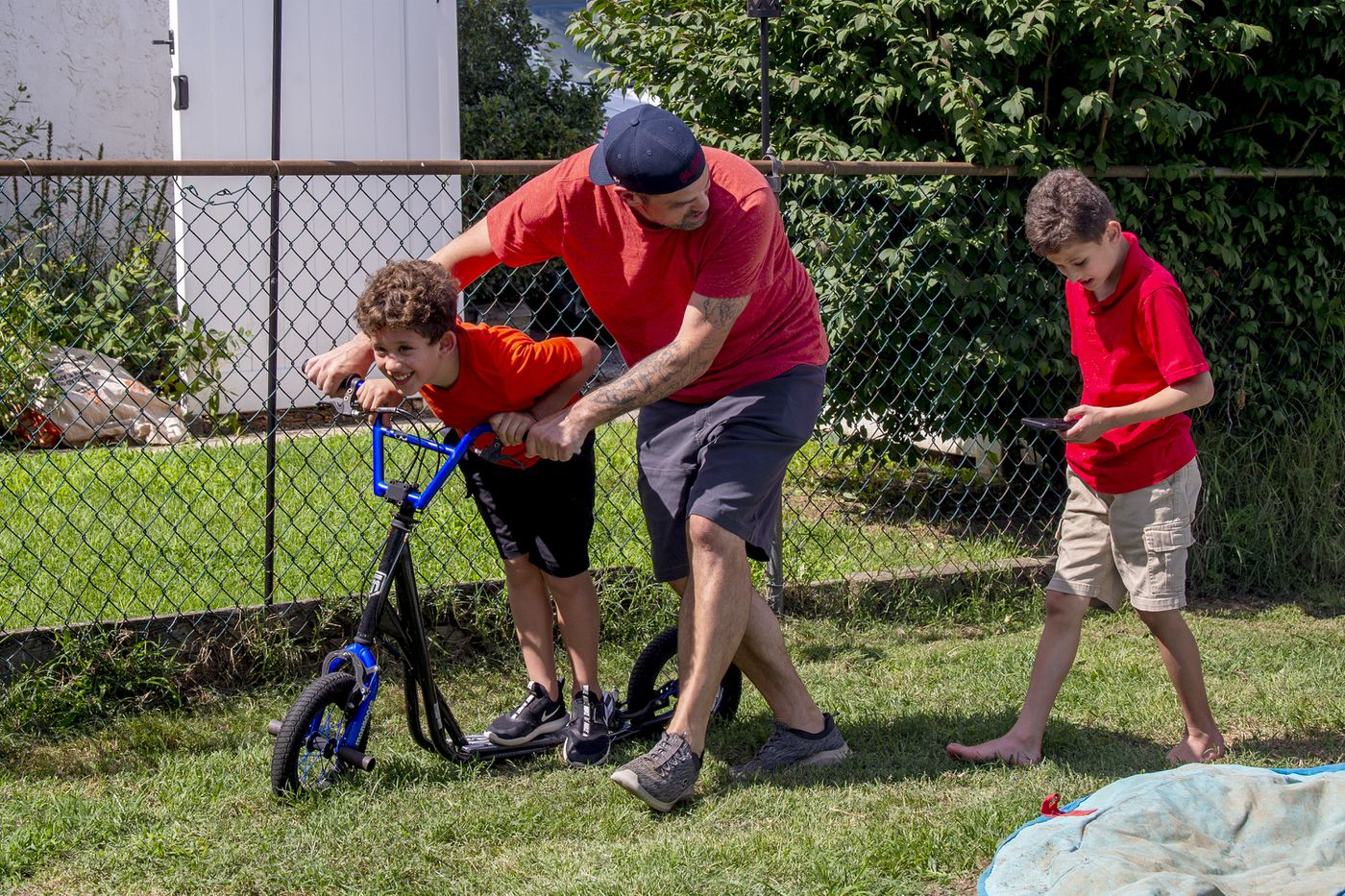 John Barchard helps his partner's son Crosby Akkawi, 8, ride his scooter in the backyard of their Conshohocken home. Behind them is Girius Akkawi, 9. Both boys have Fragile X syndrome.