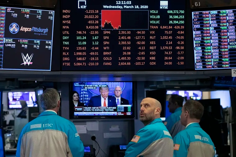 Traders at the New York Stock Exchange watching President Donald Trump's televised White House news conference on Wednesday.