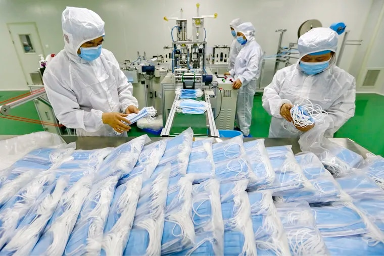 In this Feb. 7, 2020, photo, workers pack surgical masks at a factory in Suining city in southwest China's Sichuan province.