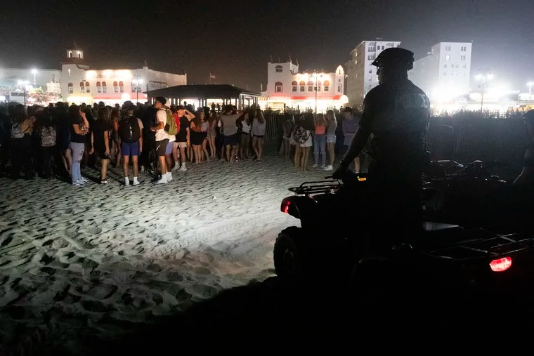 Police keep an eye on large groups of teens gathered on the beach near 11th Street in Ocean CIty, N.J. on July 27, 2021.