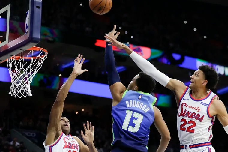 Dallas Mavericks guard Jalen Brunson, guarded by Al Horford (42) and Matisse Thybulle (22), goes in for a third-quarter layup at the Wells Fargo Center on Friday.