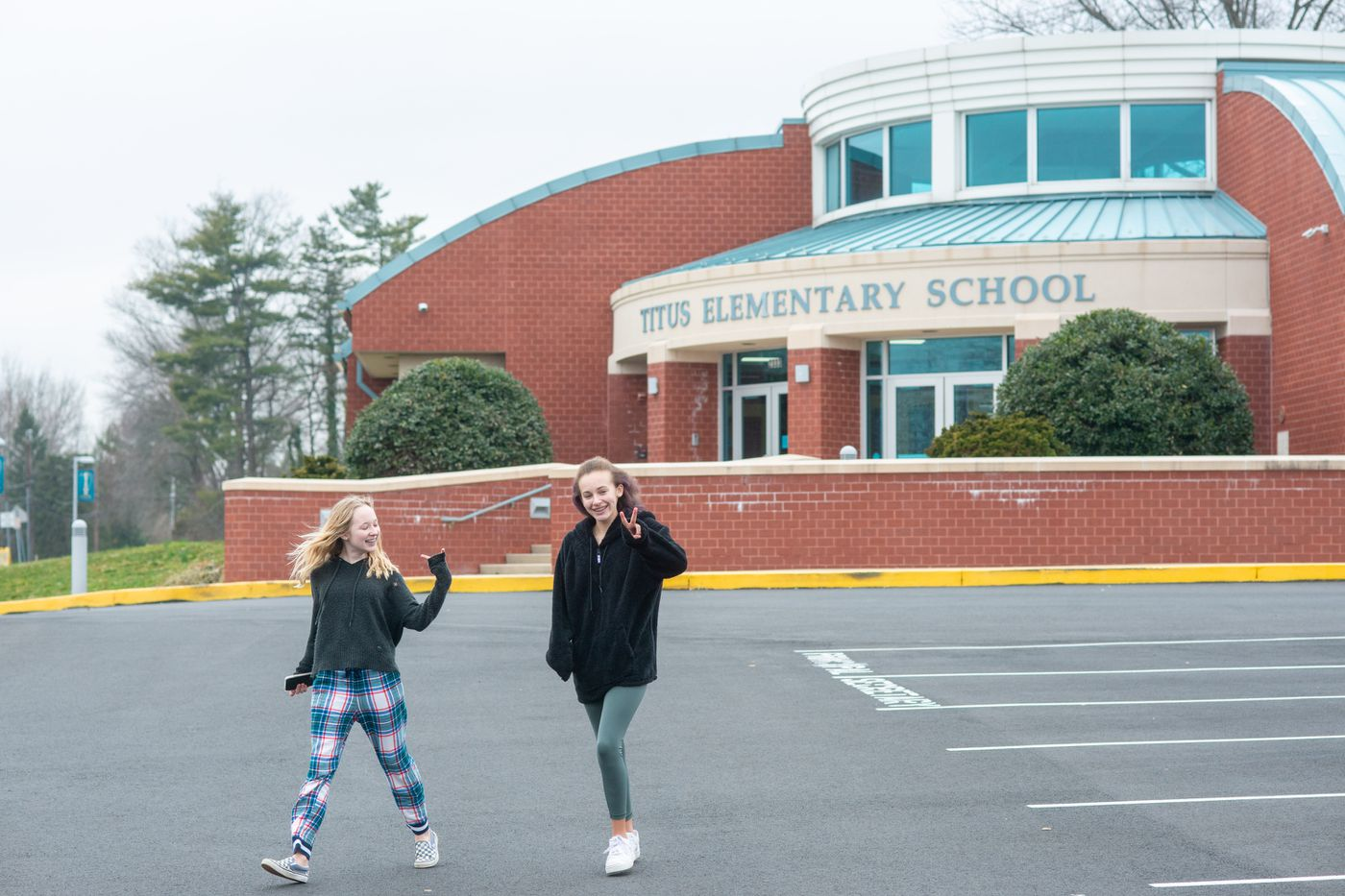 From left, Kaylyn Toerr and Gabby Long walk through the parking lot after their school was closed for the day because of a possible coronavirus threat Friday, March 06, 2020 at Titus Elementary School in Warrington. Five Central Bucks School District schools were closed for deep cleaning as a precaution and will reopen Monday March 9. WILLIAM THOMAS CAIN / For The Inquirer