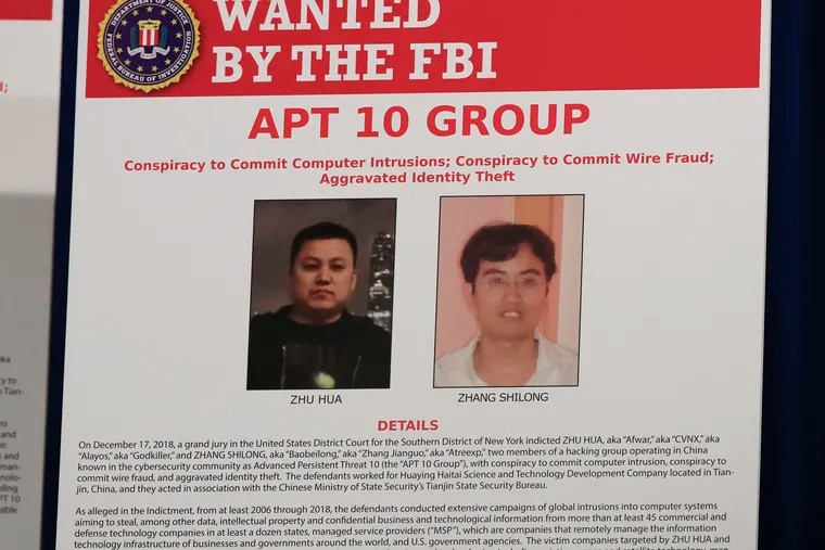 A poster displayed during a news conference at the Department of Justice in Washington, Thursday, Dec. 20, 2018, shows two Chinese citizens suspected to be with the group APT 10 carrying out an extensive hacking campaign to steal data from U.S. companies. The Justice Department is charging two Chinese citizens with carrying out an extensive hacking campaign to steal data from U.S. companies. An indictment was unsealed Thursday against Zhu Hua and Zhang Shillong. Court papers filed in Manhattan federal court allege the hackers were able to breach the computers of more than 45 entities in 12 states. (AP Photo/Manuel Balce Ceneta)