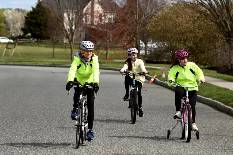 Lori Wells (from left) and her daughters Grace, 13, and Claire, 18, ride bikes in their Mullica Hill neighborhood on Tuesday. Claire has Down syndrome, and because of her history of pneumonia, the family is taking particular care with social distancing while at the same time trying to remain active with family hikes and bike rides.