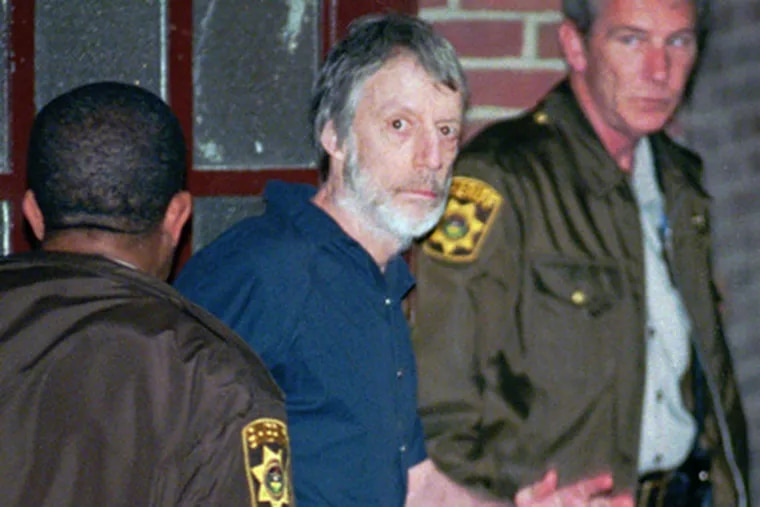 Millionaire murderer, John du Pont, waves as he is led into the holding area of the Delaware County Courthouse in Media, Pa., Thursday, May 30, 1996. du Pont died on Thursday at the age of 72. (AP Photo/Tim Shaffer)