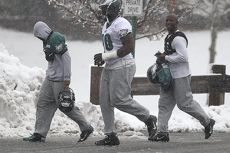 DeSean Jackson (left) Clifton Geathers (center) and Jason Avant (right) jog through the snow on their way to the indoor practice building for Tuesday's practice. (David Maialetti/Staff Photographer)