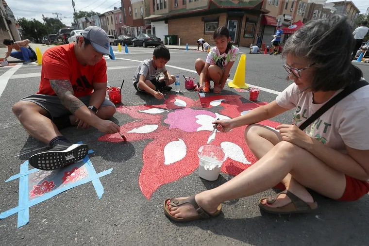 (Left to right) Dan, Jayden, Jasmine, and Kristina Chang work on a section of the mural at Seventh and Wolf Streets in Philadelphia on Sunday. The Lower Merion family joined other volunteers to paint a mural highlighting its Southeast Asian community and the area's immigrant-heavy population.