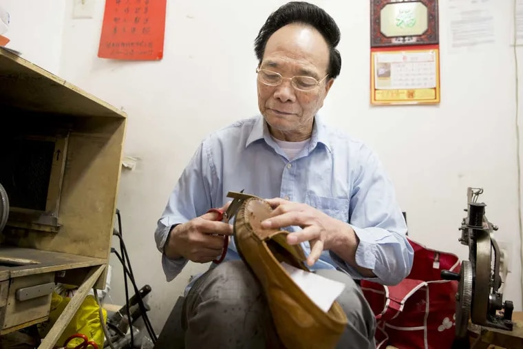 Lin Tian Fu, a legal permanent resident who emigrated from China, works in his modest repair shop near 11th and Race Streets.