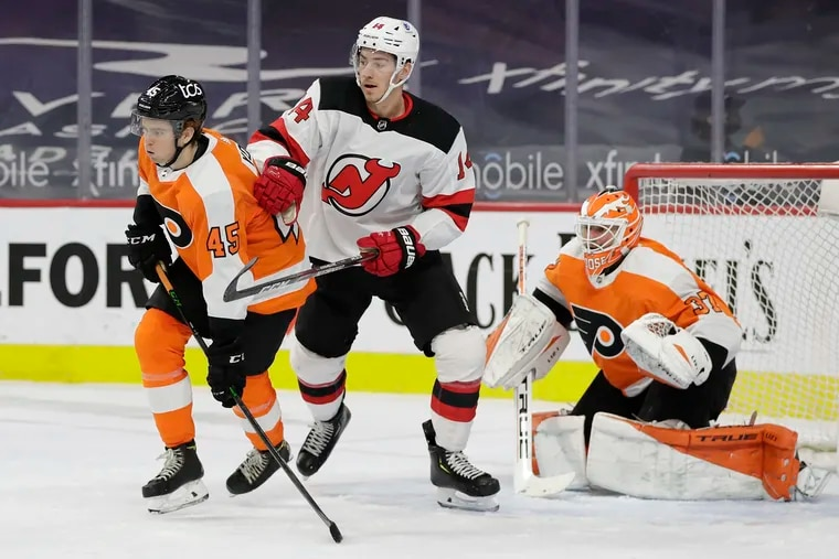 Flyers defenseman Cam York defends New Jersey Devils right winger Nathan Bastian in front of goaltender Brian Elliott in a game late last season.