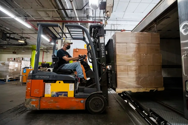 The warehouse of Share Food Program in Hunting Park has had to augment supplies during 2020.  On Wednesday, Steve Crone uses a forklift to load a truck headed to a local food pantry.