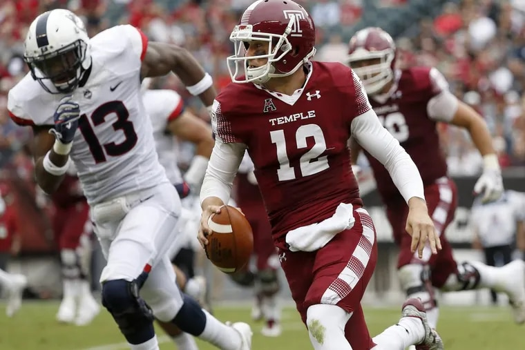 Temple's quarterback Logan Marchi, right, keeps the ball as UConn's Vontae Diggs, left, gives chase in the 2nd quarter as the Temple Owls play the UCONN Huskies in Philadelphia, PA on October 14, 2017. DAVID MAIALETTI / Staff Photographer