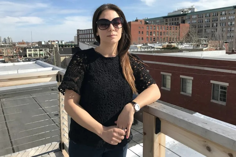 Kristin Grandzol on the roof deck of her Spring Garden home. She and her daughters are leaving the city, where they no longer feel safe after their husband and father, Gerard Grandzol, 38, was shot to death outside their home last year.