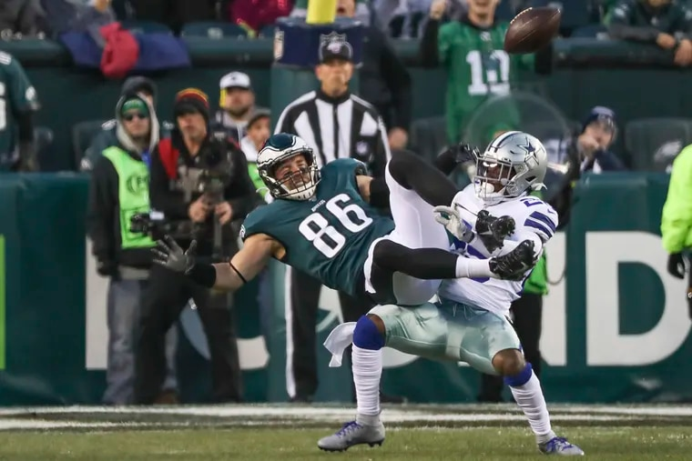 Eagles tight end Zach Ertz is brought down by Dallas Cowboys free safety Xavier Woods in the first half of a game at Lincoln Financial Field in South Philadelphia on Sunday, Dec. 22, 2019.