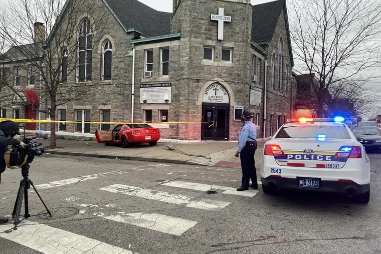 The red Ford Mustang the gunman was driving while being pursued by Philadelphia police near the intersection of Somerset and Ruth Streets in Kensington. After crashing the car, the 39-year-old man got out and ran and fired a gun at an officer who returned fire, killing him, police said.