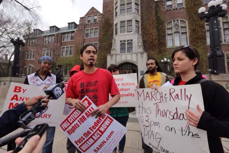 Activist Jose Alvarenga (center), national organizer of the group BAMN, or By Any Means Necessary, which challenged the ban, reads a statement critical of the decision. He spoke on the campus of the University of Michigan.