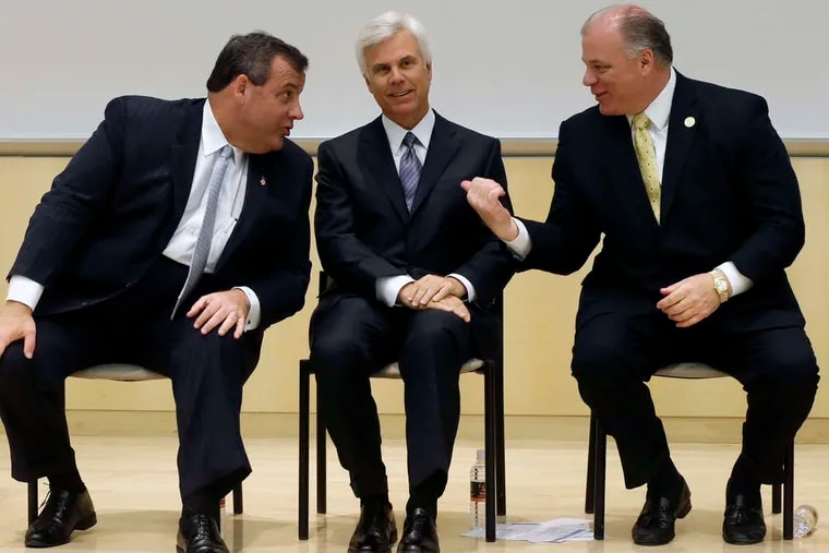 In a file photo from 2014 in Camden, former Gov. Chris Christie (left) is joined by Democratic power broker George E. Norcross III (center) and Senate President Stephen Sweeney.