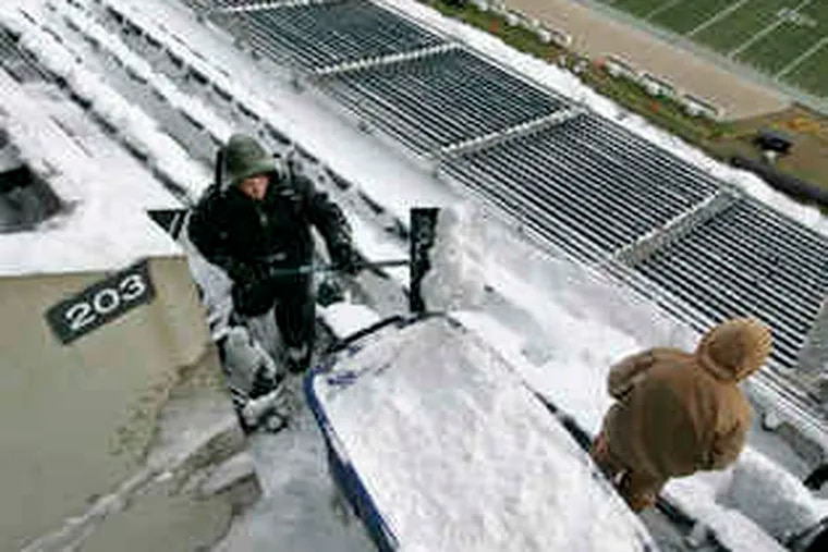 Chris Leigh shovels snow into a large blue barrel to be dumped in the Linc's upper concourse.