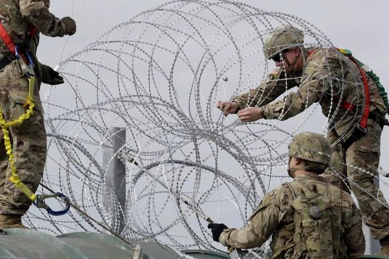 Members of the U.S.military place razor wire along the U.S.-Mexico border on the McAllen-Hidalgo International Bridge, Friday, Nov. 2, 2018, in McAllen, Texas.