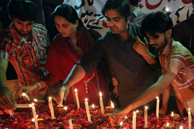 Pakistanis light candles for the victims of a bombing attack on churches in Karachi last year.