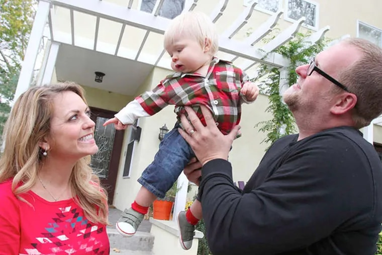 Vicky and Matt Martelli play with their son, Luka, outside their home on Baring Street in West Philadelphia. (Charles Fox / Staff Photographer)