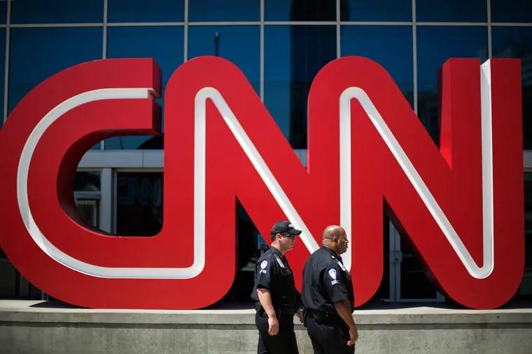Security guards walk outside CNN's headquarters in Atlanta.