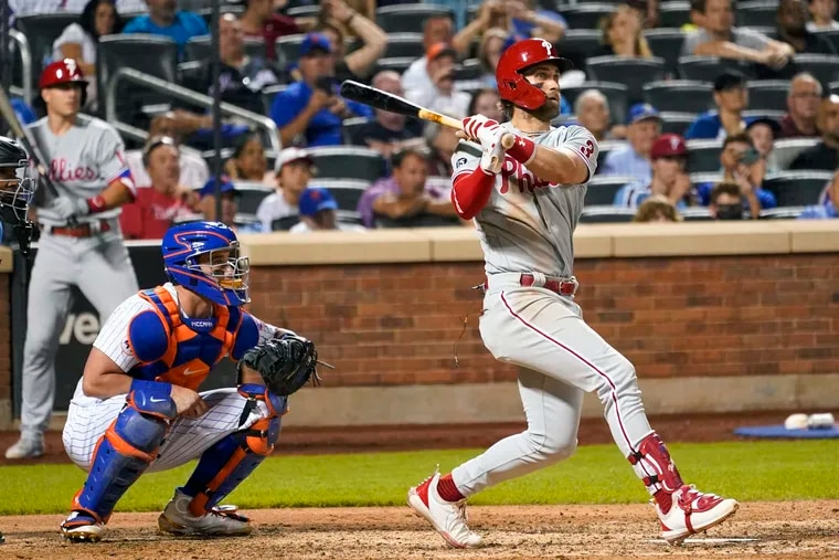 The Phillies' Bryce Harper follows through on an RBI double against the Mets on Saturday.
