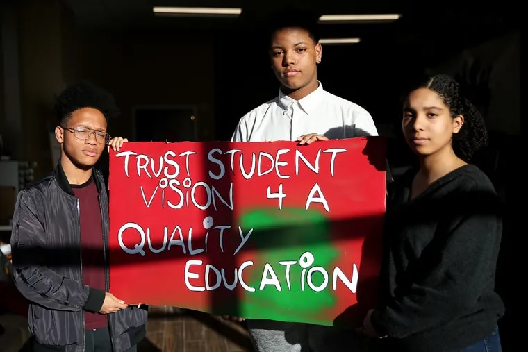 From left, Science Leadership Academy at Beeber senior Amir Curry, 18; Workshop School sophomore Charles Mitchell, 16; and Academy at Palumbo senior Nayeli Perez, 18, stand with one of their signs at the Philadelphia Student Union office in West Philadelphia. They are preparing to testify before the school board against a policy mandating the use of metal detectors in all Philadelphia School District high schools.