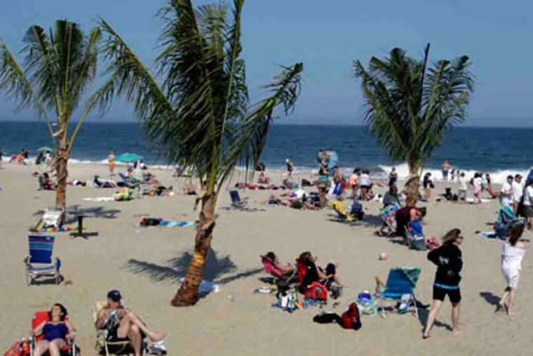 Imported palm trees and lots of sun and sand greet visitors to Point Pleasant Beach at the start of the Memorial Day weekend. (Mel Evans / Associated Press)