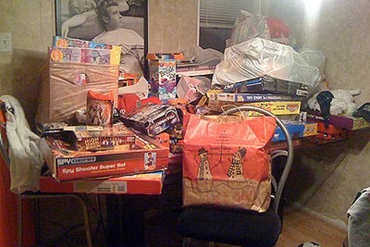 This year Billy Howell and his buddies' toy drive has been bigger than ever. Stocked on his dining room table are more than 150 toys they have collected for the children at St. Christopher's Hospital. (Photo by Kia Gregory)