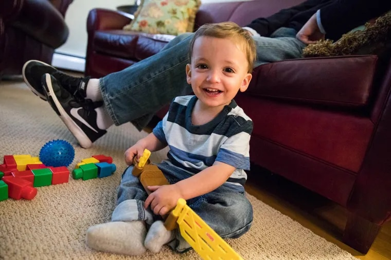 Patrick Higgins plays with his toys in his family's Newtown, Pa. living room. Patrick was adopted, his birth mother used opioids during her pregnancy.