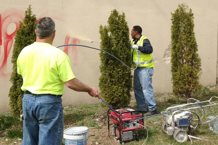SEPTA workers Ricky DeLarso and Charles Randolph paint over graffiti.