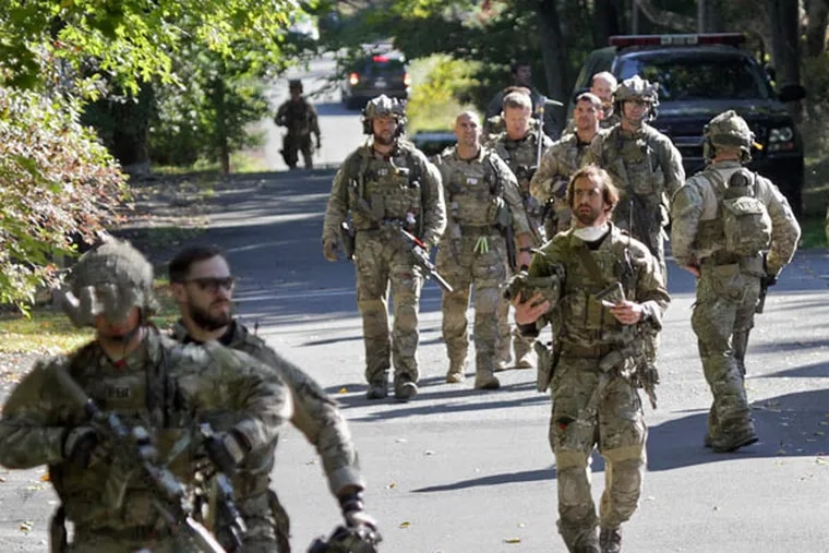 FBI along with various state police officers exit a wooded area at Buck Hill Falls in Barrett Township, Pa., where the search for Eric Frein continues Friday, Sept 26, 2014. Frein is suspected of fatally shooting a state trooper and wounding another at the Blooming Grove state police barracks two weeks ago. (AP Photo / Scranton Times & Tribune, Michael J. Mullen)