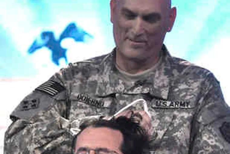 """Buzz: Comedian Stephen Colbert gets a military haircut from Gen. Ray Odierno during the taping of his """"Report"""" in Baghdad."""