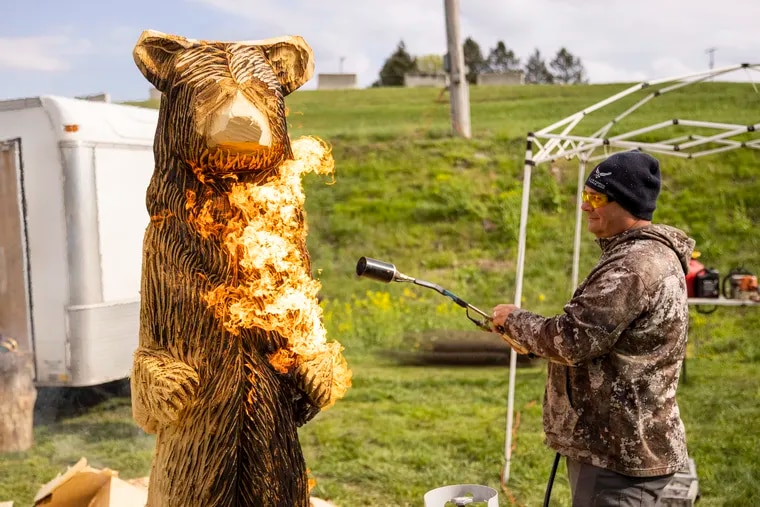 Ben Rannels, of Altoona, Pa., uses a flame to burn off excess wood and give visual texture to his 7 foot bear at the Central PA Chainsaw Carving Competition at the Shippensburg Fairgrounds in Shippensburg, Pa., last week.