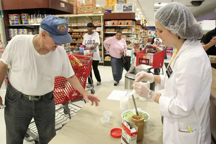 Amber Badeau, registered dietitian at the ShopRite in Olney, serves up samples of celery with peanut butter and raisins, a healthful snack. (Charles Fox / Staff Photographer)