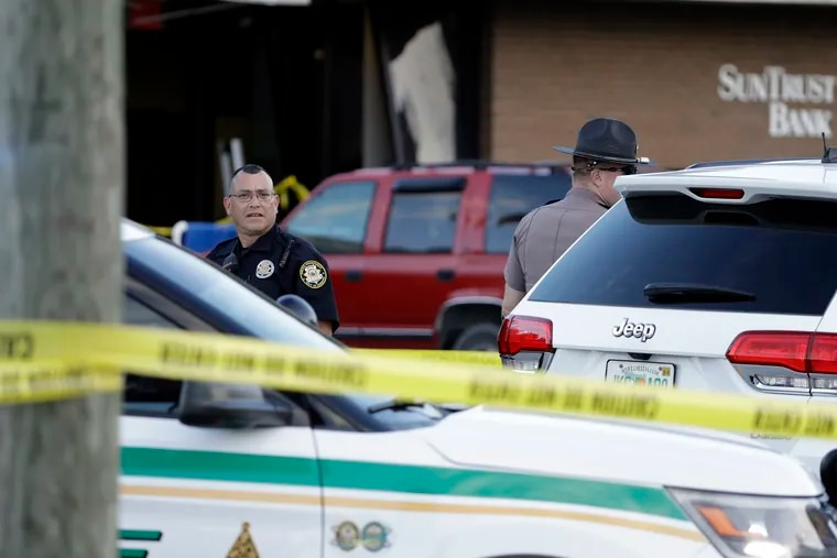Law enforcement officials stand out in front of a SunTrust Bank branch, Wednesday, Jan. 23, 2019, in Sebring, Fla., where authorities say five people were shot and killed.