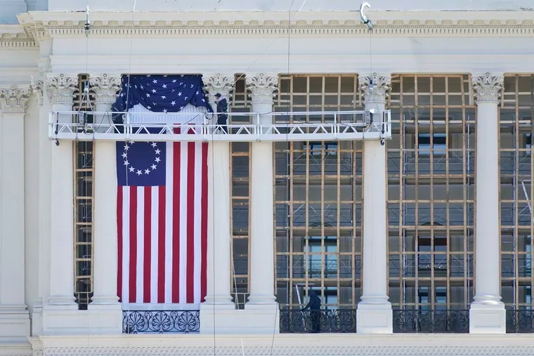 Workers install a flag on the West Front of the U.S. Capitol as preparations take place for President-elect Joe Biden's inauguration.
