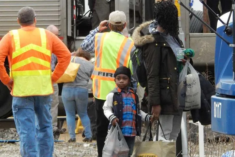 Passengers hold their belongings after being removed from the Amtrak train.