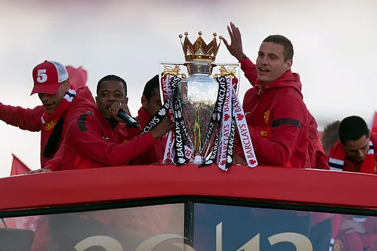 Manchester United's Nemanja Vidic and Patrice Evra hold the Premier League trophy atop the team's bus as it parades through the city. (Jon Super/AP)