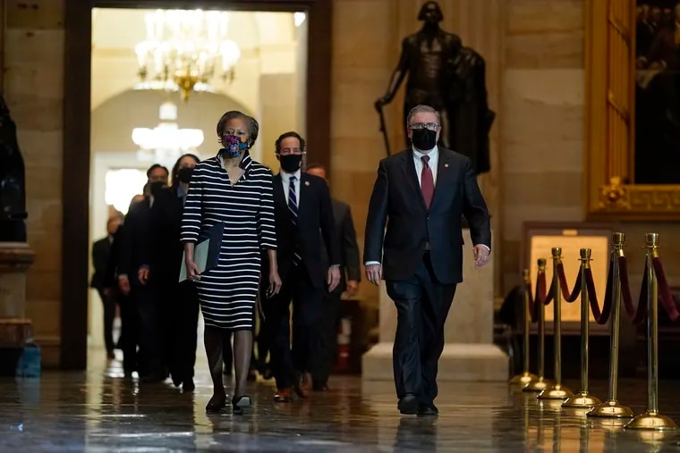 Clerk of the House Cheryl Johnson along with House Sergeant-at-Arms Tim Blodgett lead the Democratic House impeachment managers as they walk through Statuary Hall on Capitol Hill to deliver to the Senate the article of impeachment alleging incitement of insurrection against former President Donald Trump, in Washington, Monday, Jan. 25, 2021.
