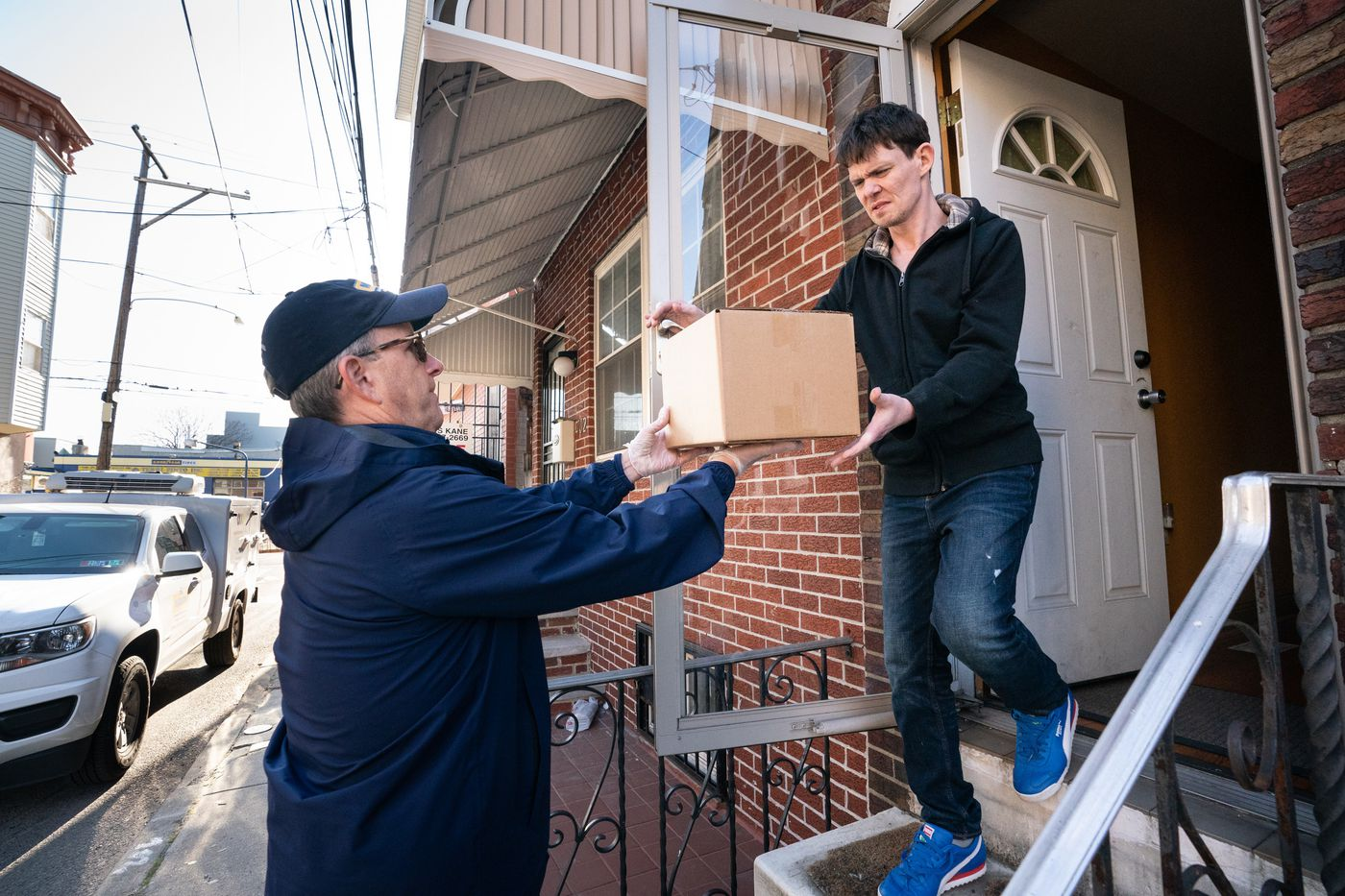 Robert Saxon, left, Director of External Affairs, makes an emergency food delivery, to client Michael Olsen, right, in Philadelphia, March 16, 2020. Saxon would normally be working in the office, but he is out making deliveries today, as the coronavirus flares, agencies like Manna that deliver food to the home-bound are facing difficulties, including the loss of volunteer drivers.