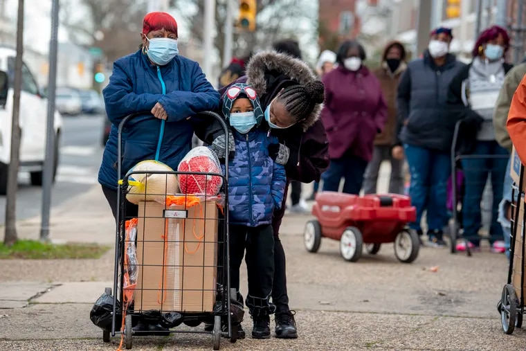 Picking up Thanksgiving meal supplies at the William Dick School in North Philadelphia Nov. 19 were four year-old Mahki Waiter and his grandmother, Beatrice Sams (left) and cousin Rhonda Flowers.