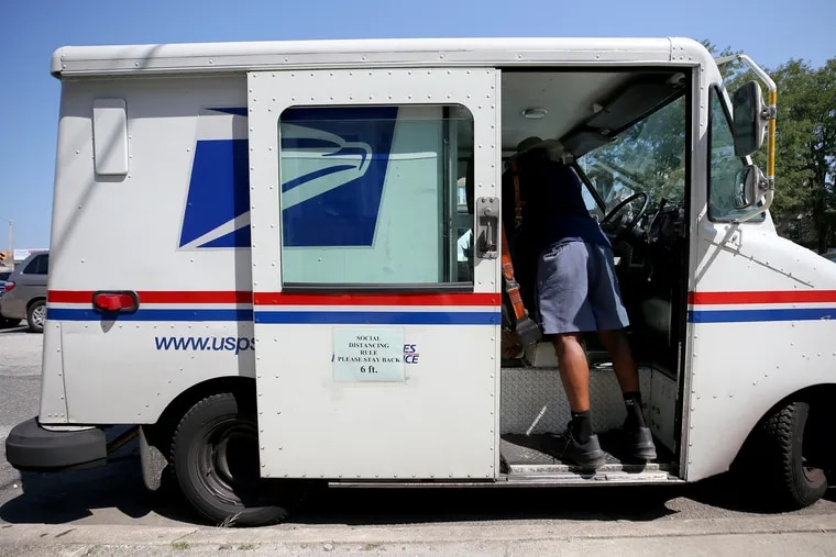 A mail carrier pulls items from his vehicle along Market Street in Upper Darby, Pa.