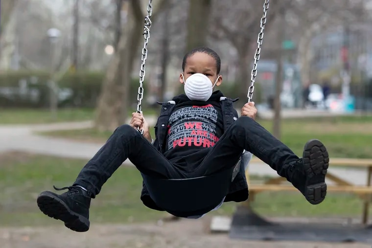 """People were making use of Clark Park in West Philadelphia to escape the concerns of the virus and to get some exercise and fresh air on March 19, 2020.  Nafi Cannady, 8, wears a mask as he swings.  His mother, Trinia Cannady, said """"The mask was for his safety and the safety of others.""""  Her philosophy for her son is """"to come out get some air and then go back inside."""""""