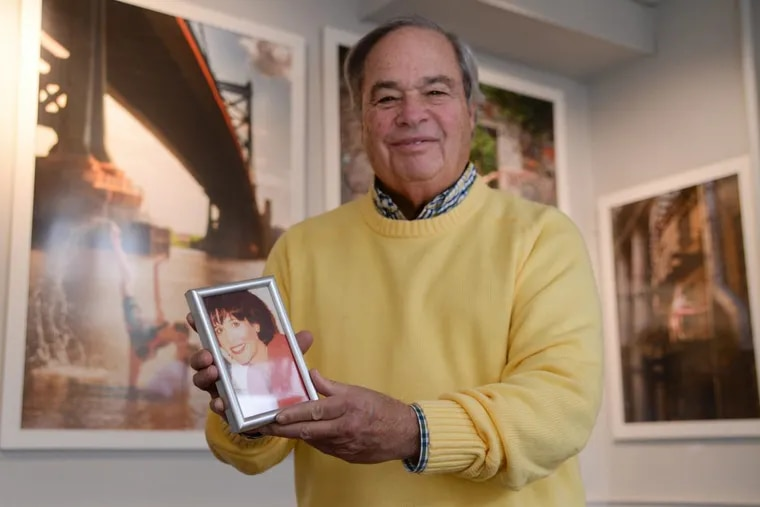 Elliot Schwartz, his gallery, and the spirit of his deceased wife, Carol, who started it all (shown in the framed photo he's holding), will  be missed in Chestnut Hill after the neighborhood mainstay closes at the end of the year.