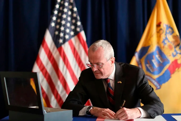 In this photo provided by the New Jersey Office of the Governor, N.J. Gov. Phil Murphy signs the Medical Aid in Dying for the Terminally Ill Act Friday, April 12, 2019 at the New Jersey Statehouse in Trenton, N.J. New Jersey is the eighth state to enact a law permitting terminally ill patients to seek life ending medication. (New Jersey Office of the Governor via AP)