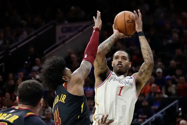 Sixers forward Mike Scott shoots over Cleveland Cavaliers guard Kevin Porter Jr.