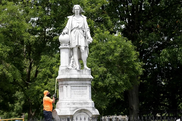 A worker takes a measurement as they prepare to box the Christopher Columbus statue in Marconi Plaza in Philadelphia, Pa. on June 16, 2020.