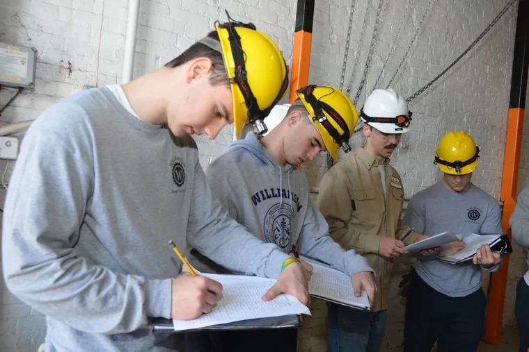 Seniors at Williamson College of the Trades often serve as mentors to underclassmen, sharing their knowledge. The power plant technology senior in the brown shirt, is instructing underclassmen in the college's power plant.