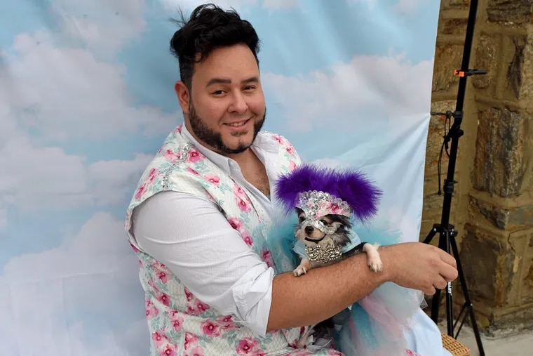 Fur dad Roberto Negrin poses with Athena, one of his five Chihuahuas, in the front yard of their Juniata Park home.